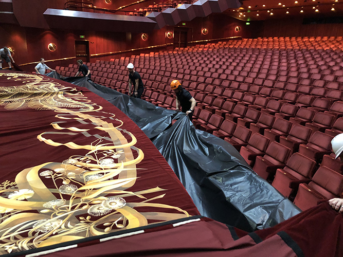 Production crew paging out the curtain